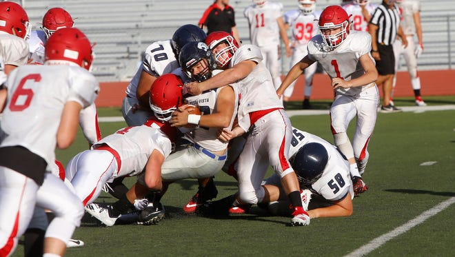 Piedra Vista's McKay Cook fights to stay on his feet against Durango during Friday's scrimmage at Hutchison Stadium. Visit daily-times.com this week for the latest sports results, video and photo galleries.