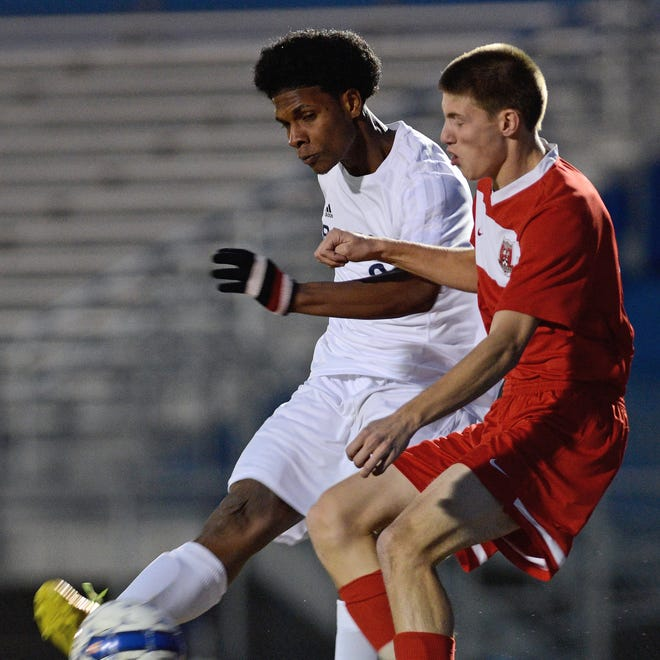 Bay Port's Jahvarn Robinson makes a pass around Pulaski's Ryan Hansen in the first half of Tuesday's FRCC match at Bay Port High School.