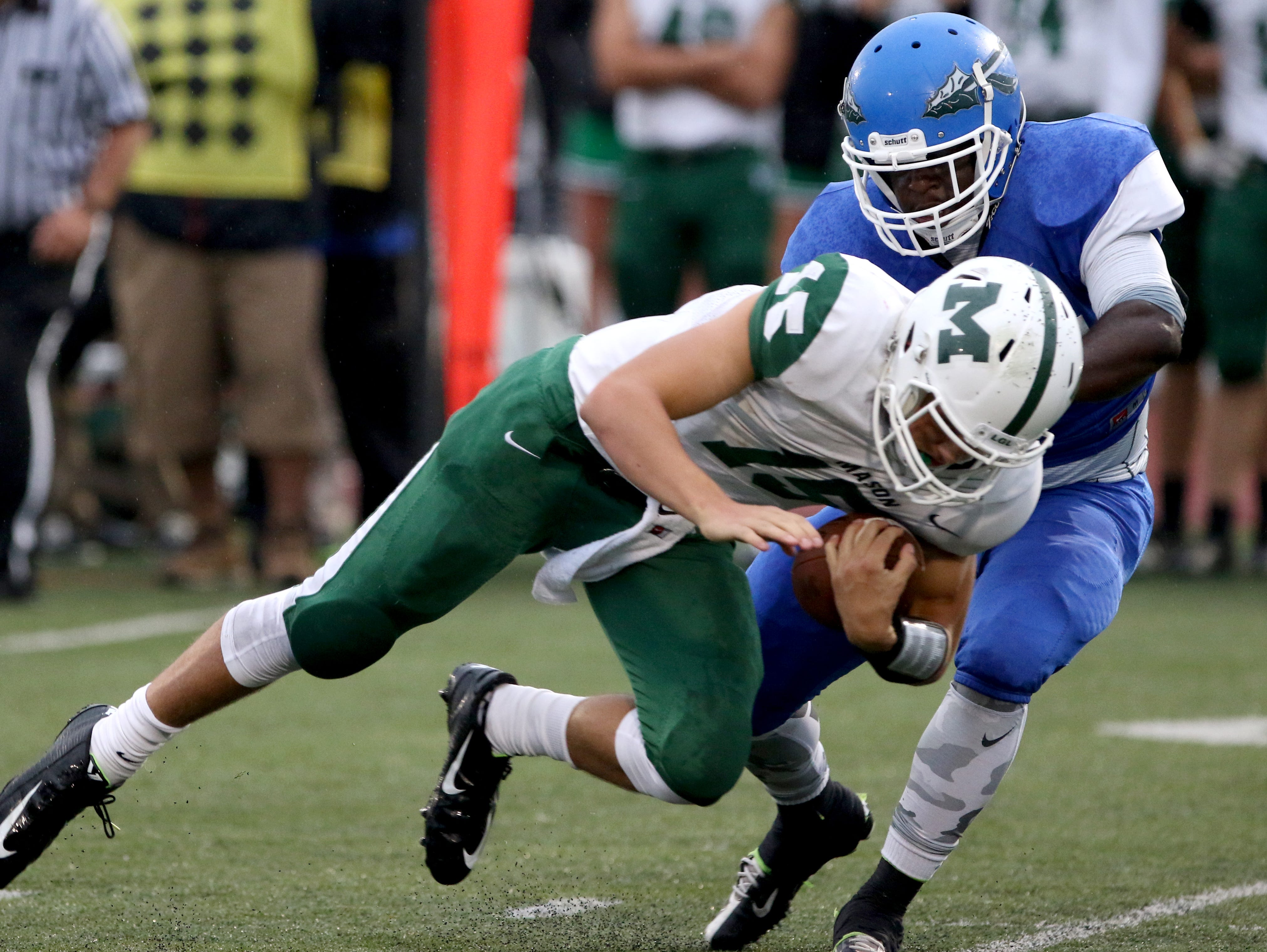 Mason quarterback Preston Hutchinson is sacked by Winton Woods' Kwamane Watson in the first half at Winton Woods High School Friday September 11, 2015.