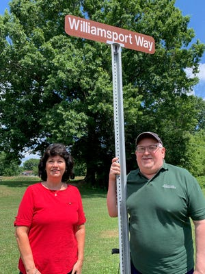 Alliance Historical Society president Michelle Dillon, left, and former society board member Dan Skivolocke standing next to one of two newly erected signs on River Street honoring the former Williamsport Village, which was located on the north side of Alliance surrounding the intersection of Webb Ave. and River St.