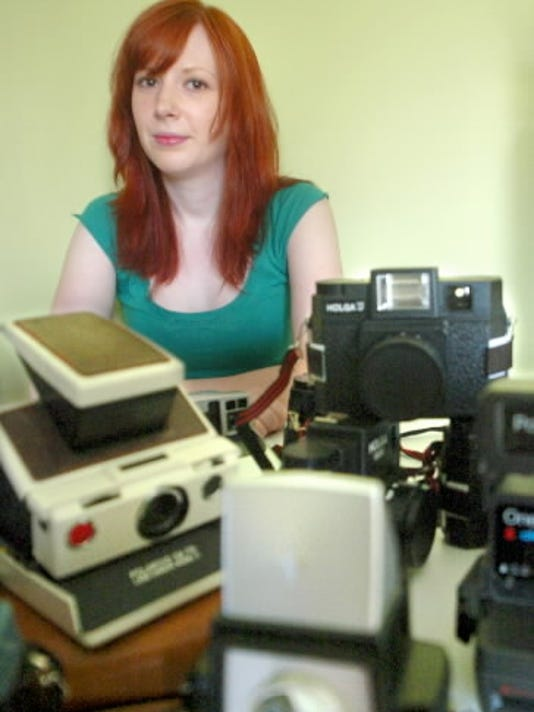 Erin Gibson of Springettsbury Township sits in her office with part of her collection of old cameras in this 2010 file photo.