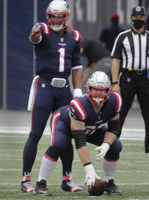 Joe Thuney, who was the surprise starter at center in the absence of injured regular David Andrews, prepares to snap the ball to Cam Newton during Sunday's game against the Raiders at Gillette Stadium.