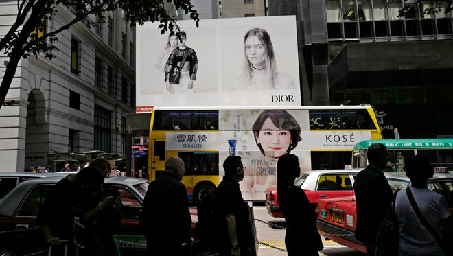 People walk past a fashion advertising in Hong Kong, Wednesday, April 5, 2017.