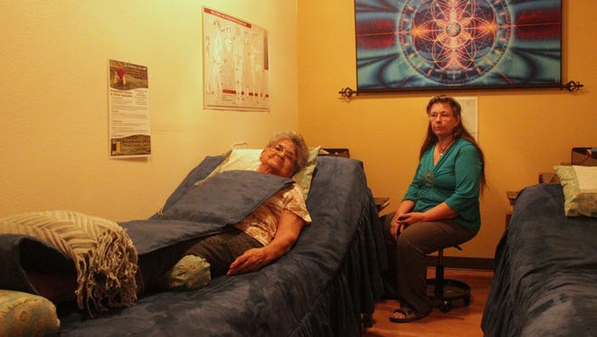 CAPPED Founder and Executive Director Tres VanWinkle looks on as Lupe Ash receives Bio-Regulation Therapy, a form of electro-magnetic field therapy, at the CAPPED office at 907 New York Avenue.