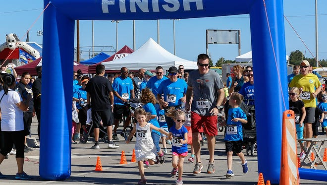 Isobel Healy and Molly McPhee hold hands as they, Matt Chisam and Easton Chisam start the inaugural No Child Wet Behind Family Fun Run on Saturday morning.
