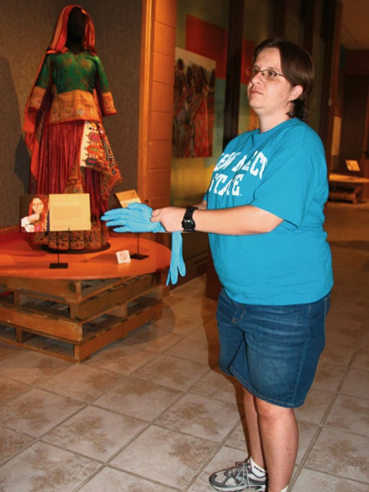 Intern Crystal Mahaffey demonstrates how a condition report is performed in an exhibit at the Carlsbad Museum and Arts Center on Wednesday.