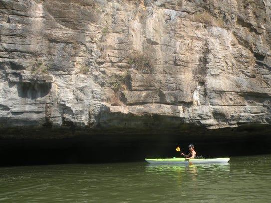 Betty Glenn paddlers her kayak before a cliff along