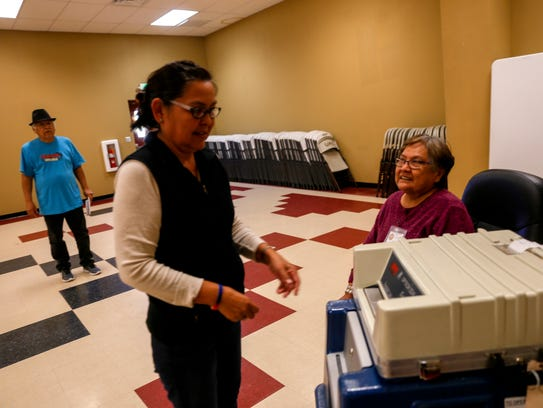 Election worker Chris Johnson, right, registers ballots Tuesday at the Upper Fruitland Chapter house.
