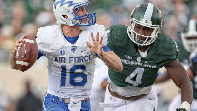 Air Force Falcons quarterback Karson Roberts has pass hurried by Michigan State Spartans defensive lineman Malik McDowell during the 2nd half of a game at Spartan Stadium. MSU won 35-21.