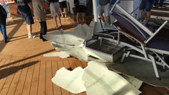Passengers walk around debris on the top deck of Royal