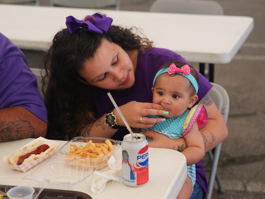 Lus Nieves (left) helps her 8-month-old daughter, Ava, with her french fries. She came to the event with her husband and other two young daughters.