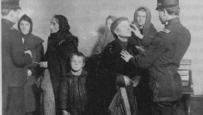 Immigration officer at Ellis Island checks a women's eyelids for signs of an infection.