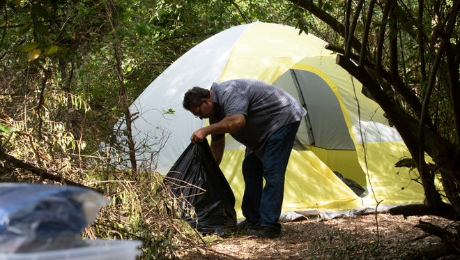 Reverand Steve Brigham works on cleaning out one of the now empty tents as he and others work to prepare the camp for closing. The land on which the Howell homeless camp is located has been sold and the homeless must leave in the near future.