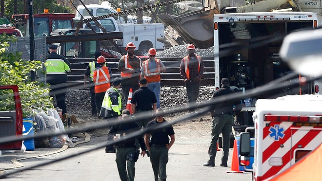 A rail track, top left, is pulled by a front loader as workers labor at the site where a deadly train derailment happened earlier in the week, Friday, May 15, 2015, in Philadelphia. Amtrak is working to restore Northeast Corridor rail service between New York City and Philadelphia. Service was suspended after a train derailed in Philadelphia on Tuesday night, killing eight passengers and injuring more than 200. (AP Photo/Julio Cortez)