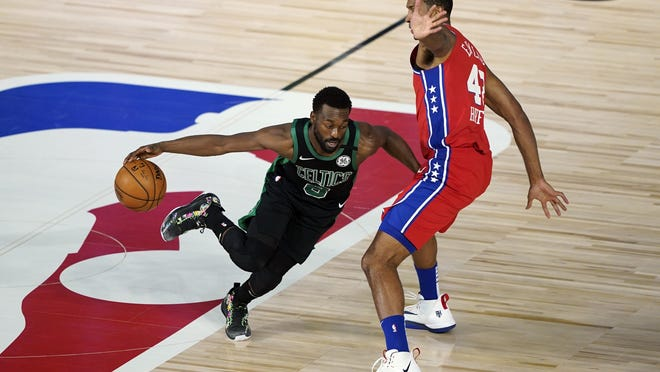 Boston's Kemba Walker, left, drives toward Philadelphia's Al Horford during the first half of Monday's game.