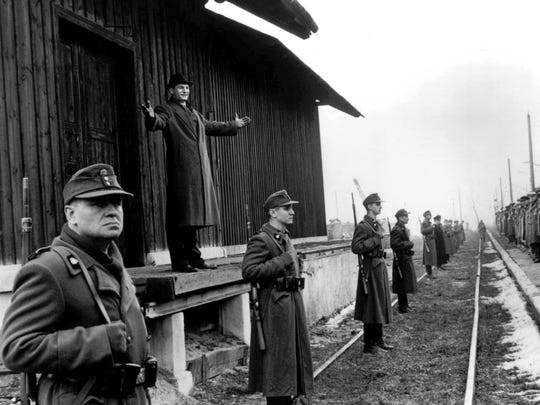"""In """"Schindler's List,"""" German industrialist Oskar Schindler, played by Liam Neeson (on platform), welcomes his workers to the safety of his new factory at Brinnlitz, Germany."""