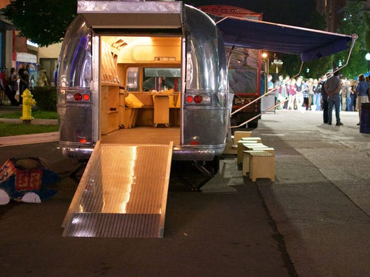 The Mobile Collaboratory sits at a local street fair showing an exhibit of public interest design projects.