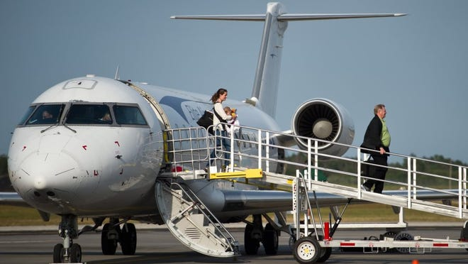 Meghan Carson, left, of New York City, carries her 7-month-old daughter, Ellie Carson, as she disembarks an Elite Airways flight on March 17, 2016, arriving in Vero Beach from Newark Liberty International Airport. They flew to Vero Beach to visit Ellie's grandmother, Deidre Renehan.