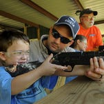 """Carter Clayton gets hands on instructions for shooting a BB gun from Kyle Martin at the National Wild Turkey Federation """"Jake's Day for Kids""""."""