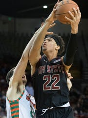 New Mexico State's Eli Chuha takes the ball in the post against UTRGV's Mike Hoffman late in the second half Saturday night at the Pan American Center.