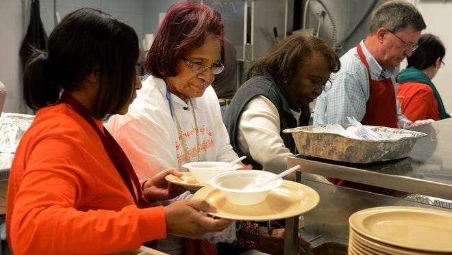 Shirley Love (center) helps serve chili that she prepared and donated to the Regional Inter-Faith Association's soup kitchen Friday.