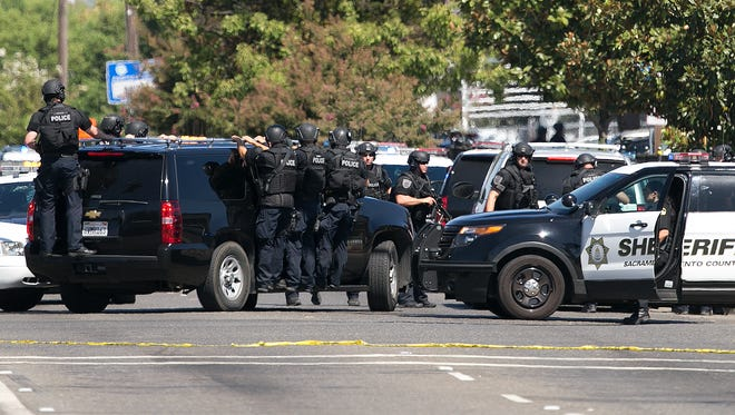 Law enforcement officers in tactical gear arrive at the scene were suspects believed to be involved in the shooting of three law enforcement officers, Wednesday, Aug. 30, 2017, in Sacramento, Calif.
