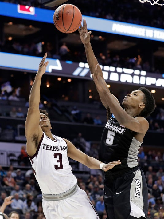 Texas A&M's Admon Gilder (3) shoots over Providence's Rodney Bullock (5) during the second half of a first-round game in the NCAA men's college basketball tournament in Charlotte, N.C., Friday, March 16, 2018. (AP Photo/Gerry Broome)