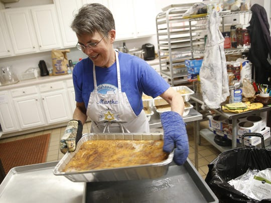 Martha Billings pulls a pan of kugel out of the oven in the kitchen at Temple Israel, where a volunteer staff is working to create 25 pans worth of kugel for the thousands of expected attendees of their 7th Annual Tallahassee Jewish Food and Cultural Festival on Sunday.