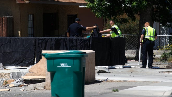 Farmington police officers secure a residence where a woman was struck and killed by a vehicle Thursday in the 700 block of West Apache Street in Farmington.