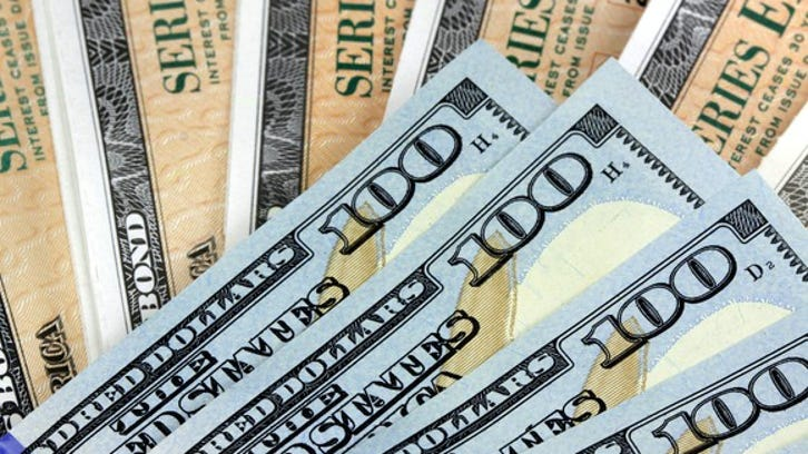 A fanned pile of hundred dollar bills atop a fanned stack of Treasury bonds.