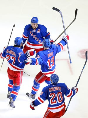 New York Rangers defenseman Ryan McDonagh (27) reacts with New York Rangers center Derek Stepan (21) New York Rangers right wing Jesper Fast (19) and New York Rangers left wing Chris Kreider (20) after scoring the game-winning goal against the Washington Capitals during the overtime period of game five of the second round of the 2015 Stanley Cup Playoffs at Madison Square Garden.