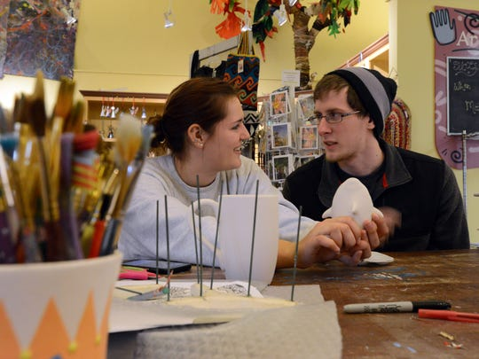 Lillia Sammler, left, and Dustin Boyer try to decide to paint a ceramic shark Wednesday at Art and Clay on Main in downtown Lancaster. Art and Clay is one of the many downtown businesses taking part in Destination Downtown Lancaster's passport program.