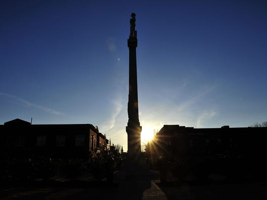 The Sun sets behind the statue of the marble Confederate