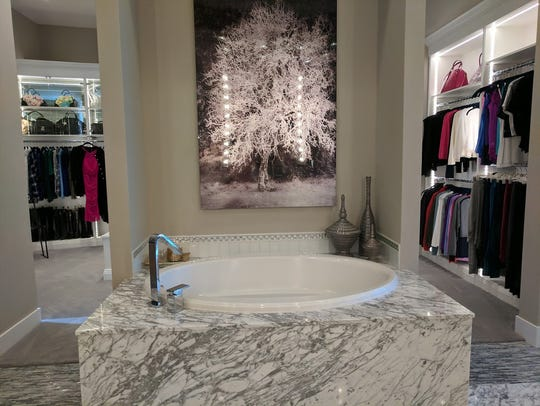The master bathroom is anchored by a marble-encases