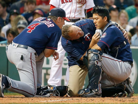 Minnesota Twins manager Paul Molitor (4) and a trainer tend to Kurt Suzuki, right, who was injured on a pitch during the second inning of a baseball game against the Boston Red Sox in Boston, Saturday, July 23, 2016. Suzuki left the game. (AP Photo/Michael Dwyer)