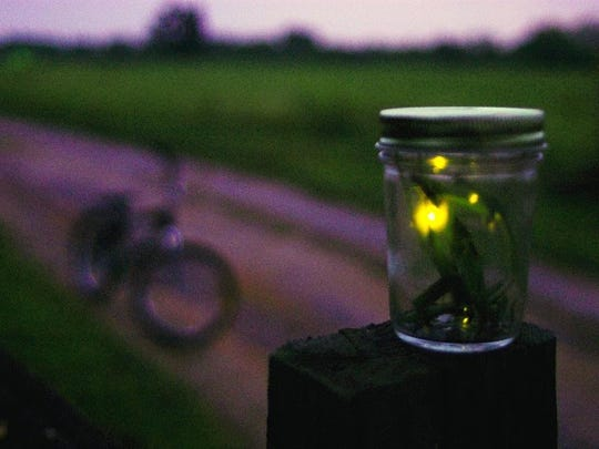 A jar of lightning bugs gathered by young boys sits on a post in Sherer, N.C.