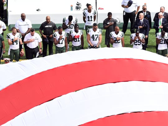 New York Jets players stand for the National Anthem with the field-size flag on display.