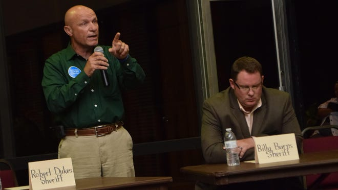 Robert Dukes (left), a candidate for Rapides Parish sherieff, speaks at a Thursday night forum in Pineville. At right (seated) is Billy Burns, another sheriff candidate.