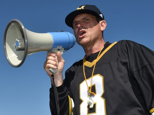 Jim Harbaugh encourages the more than 500 high school football players in their speed drill at a Michigan Satellite Camp at Pearl High School in Pearl, Miss. There may be no louder voice in college football.
