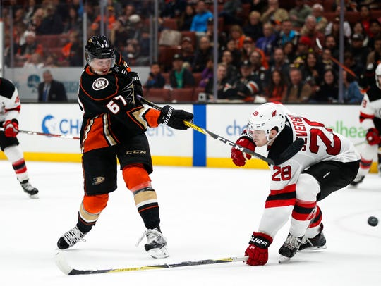 Anaheim Ducks' Rickard Rakell, left, of Sweden, shoots