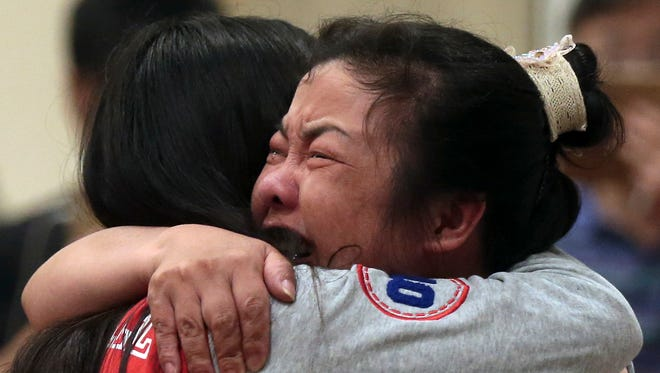 In this photo taken Tuesday, June 2, 2015, two woman cry and hug each other at hotel where relatives of passengers trapped in an capsized cruise ship gathered in Nanjing in east China's Jiangsu province. Hopes dimmed Wednesday for rescuing more than 400 people still trapped in a capsized river cruise ship that overturned in stormy weather, as hundreds of rescuers searched the Yangtze River site in what could become the deadliest Chinese maritime accident in decades. (Chinatopix Via AP) CHINA OUT
