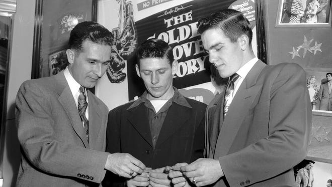 """January 23, 1951 - Golden Gloves took over the Strand Theater on Jan. 23, 1951, for the first showing of """"The Golden Gloves Story."""" Champs and runnersup in the city tournament were present and received medals, including Stanley Gregory (right), novice light heavyweight, and Irving Tucker Jr. (center), open flyweight. The boxers show their awards to Carroll Beasley (left), manager of the theater."""