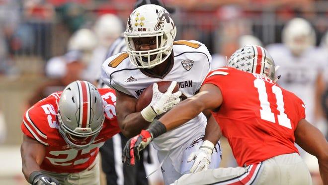 Western Michigan's Jamauri Bogan splits through the defense of Ohio State's Tyvis Powell  and Vonn Bell in the third quarter of OSU's win Saturday in Columbus, Ohio.