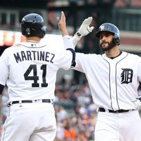 Tigers rightfielder J.D. Martinez hits a two-run home run and celebrates with teammate Victor Martinez during the second inning Friday at Comerica Park.