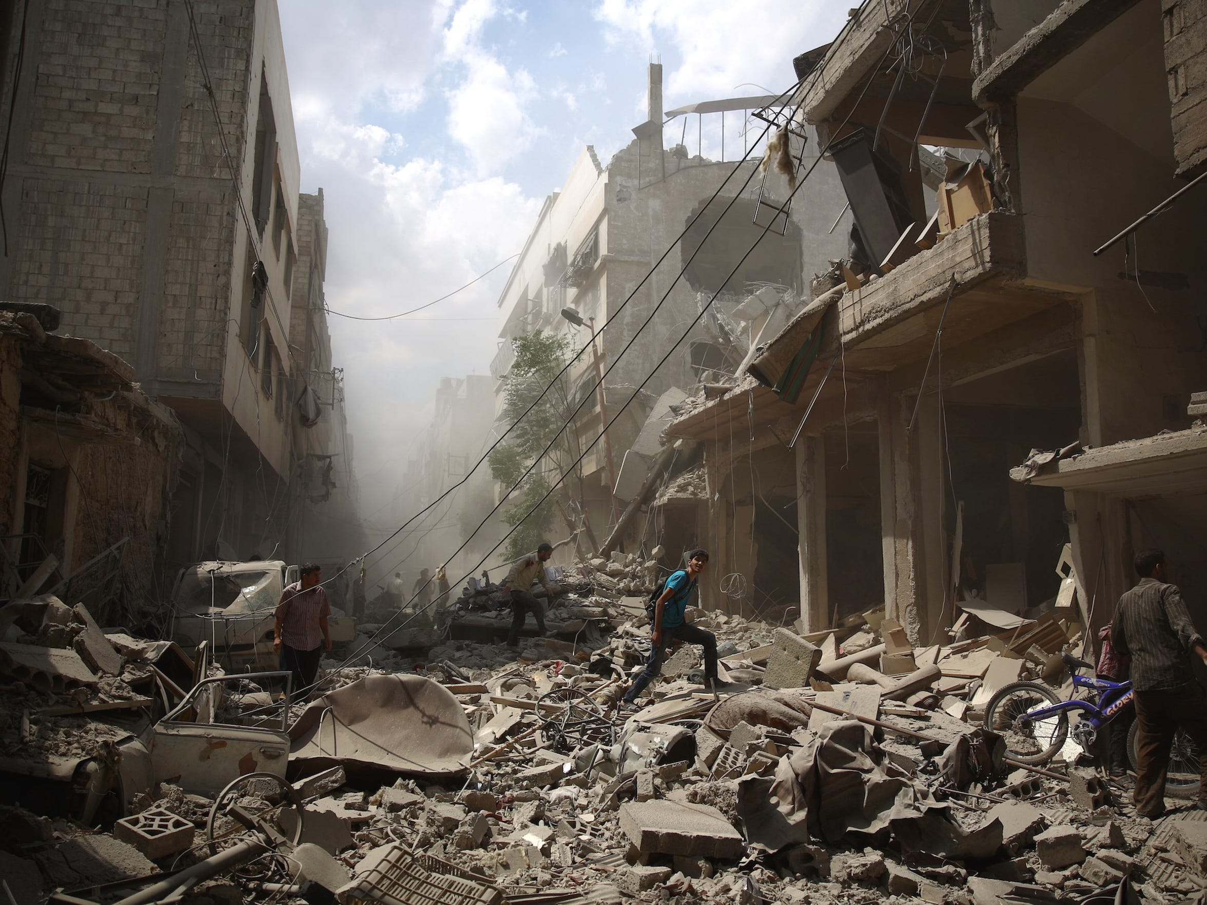 Syrians walk amid the rubble of destroyed buildings following reported air strikes by regime forces in the rebel-held area of Douma, east of the capital Damascus, on Aug. 30, 2015.