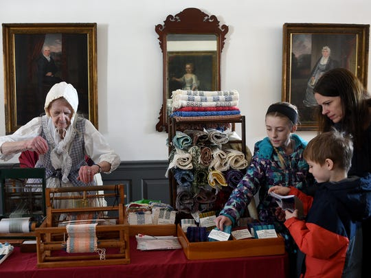 Lois Macknick of Annandale handweaves on a loom while Grace Visscher 10, Gerrit Visscher 7, and their mother Laura looks at Macknick's creations at Dey Mansion in Wayne on Sunday, February 18, 2018.
