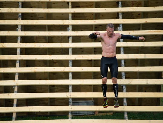A runner launches himself off the last wall obstacle