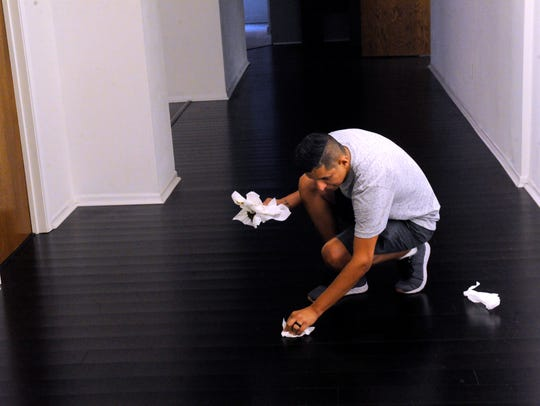 Abel Perez picks-up after his dog Thursday, Aug. 10,
