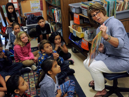 "Fourth-graders at Jackson Elementary School listen to Penny Parker Klostermann as she reads from her new book ""A Cooked-Up Fairy Tale,"" Wednesday Aug. 30, 2017. It is her second children's book after her 2015 release of ""There Was an Old Dragon Who Swallowed a Knight,"" sitting on the book case behind her."