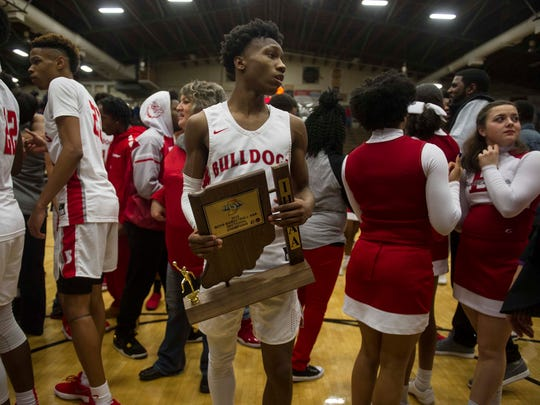 Bosse's Mekhi Lairy holds on to the sectional championship trophy after defeating Memorial in the Class 3A Boonville Sectional final at Boonville High School on Saturday, March 3, 2018. Bosse defeated Memorial 67-62.